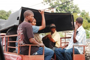 Haitian Men riding a Tap tap